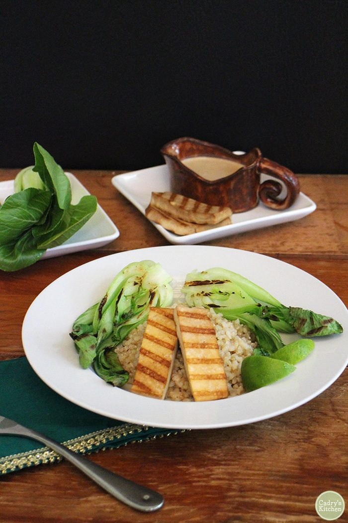 Slabs of grilled tofu over brown rice with grilled bok choy in bowl.