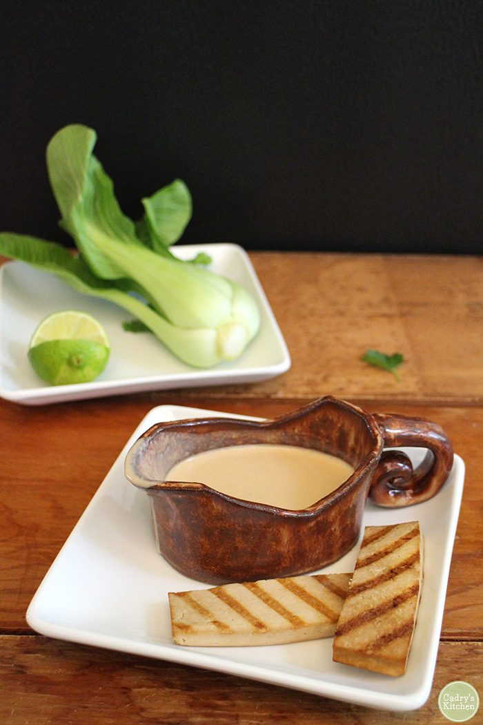 Peanut sauce in gravy boat by grilled slabs of tofu satay.