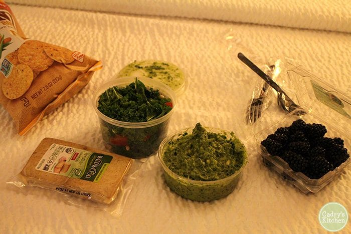 Bed picnic with tofu, salad, berries, and kale guacamole.