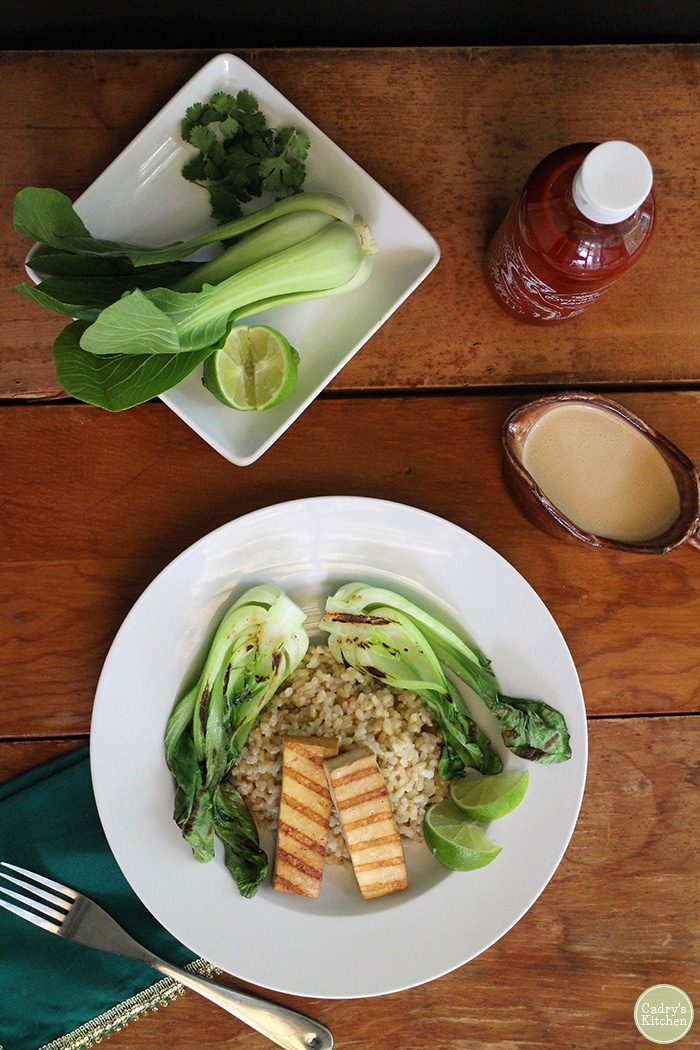 Overhead grilled tofu on table, bok choy, hot sauce, and peanut sauce in gravy boat.