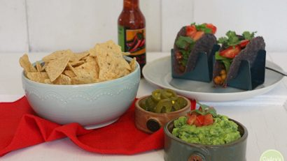 Kale guacamole in bowl with chips, tacos, and hot sauce.