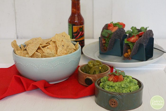 Bowl of kale guacamole with tacos, tortilla chips, and hot sauce.