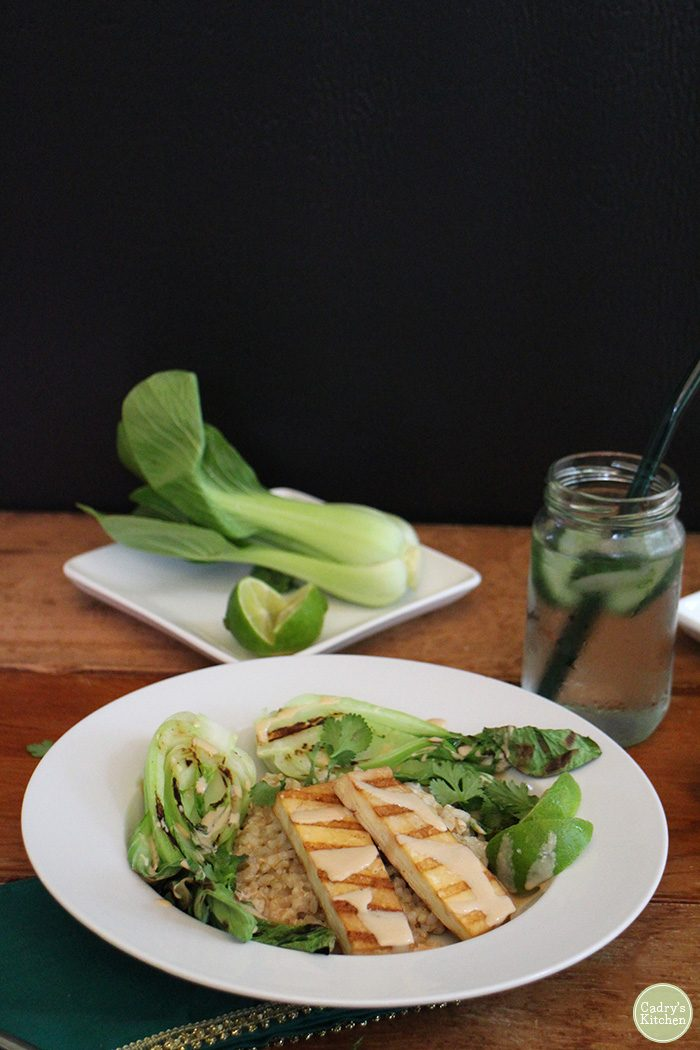 Grilled tofu satay & bok choy in bowl, drizzled with peanut sauce.