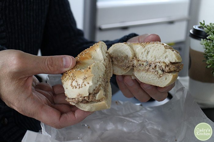 David's hands holding a bagel with walnut cinnamon tofu spread.