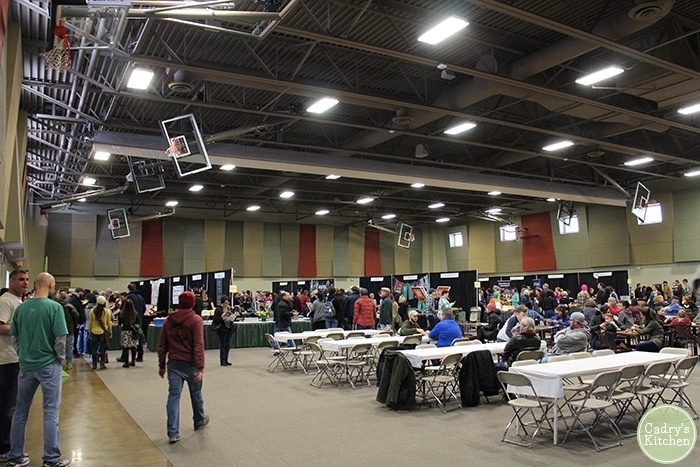 Vegan Fest 2018. People standing in large room with vendors & tables.