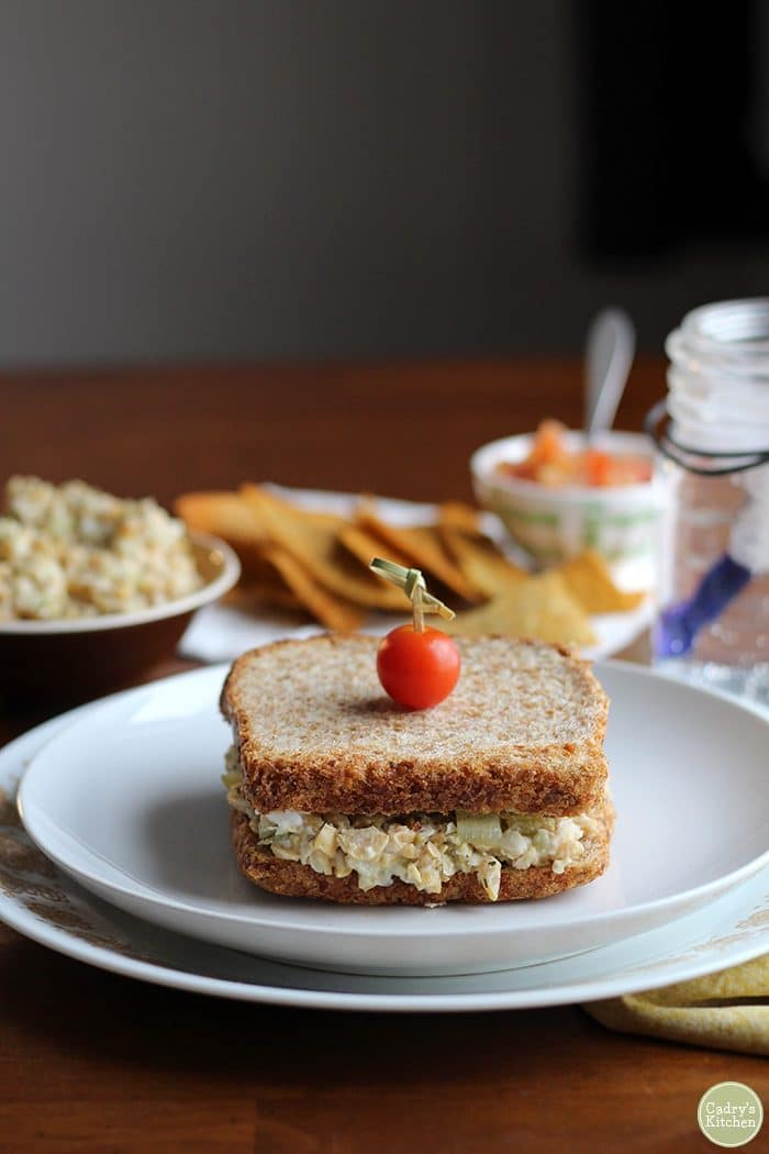 Vegan tuna salad sandwich with chickpeas on plate with chips & salsa.
