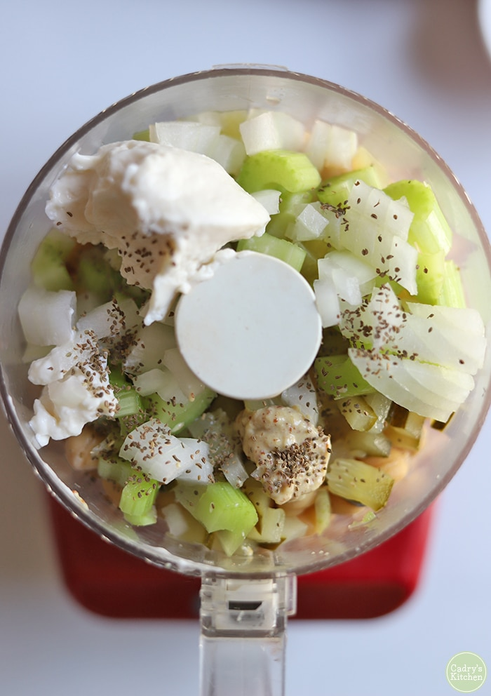 Overhead food processor with vegan mayo, celery, celery seed, onion, and chickpeas.