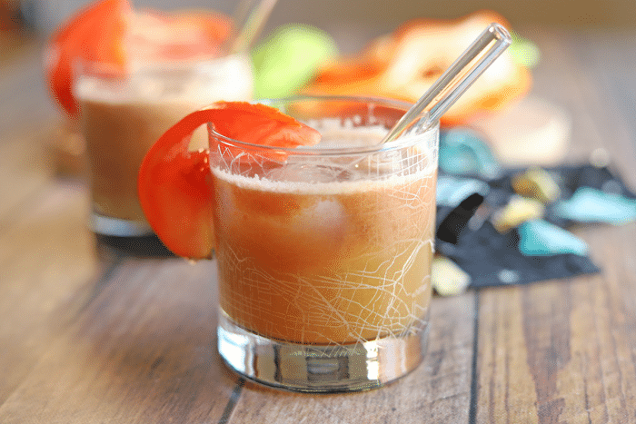 Glass of juice on table with tomato garnish.