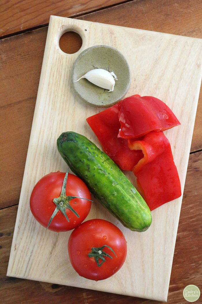 Tomatoes, cucumber, bell pepper pieces, and garlic clove on cutting board.