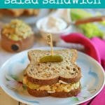 Text: Vegan tuna salad sandwich. Chickpea salad sandwich on plate with pink napkin.