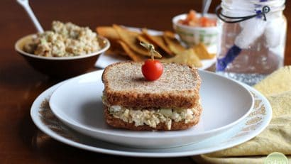 Chickpea-based vegan tuna salad on plate with cherry tomato on top.
