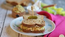 Chickpea salad sandwich on plate with pickle on top.