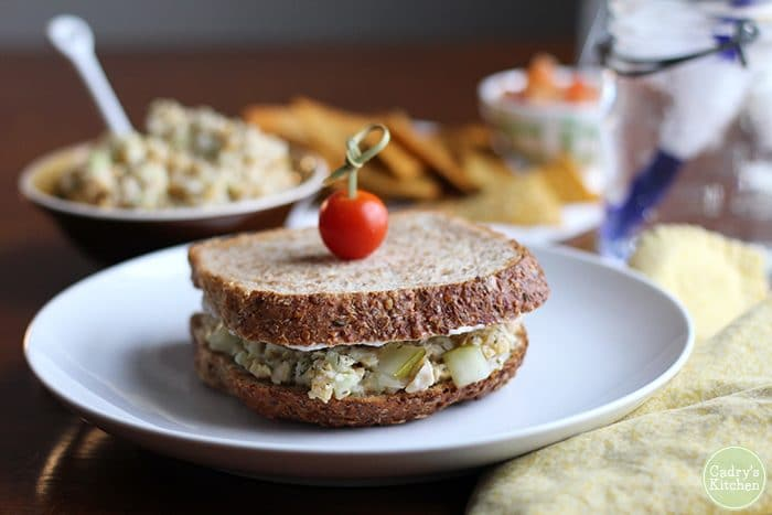Vegan tuna salad made with chickpeas on plate with cherry tomato speared through it.
