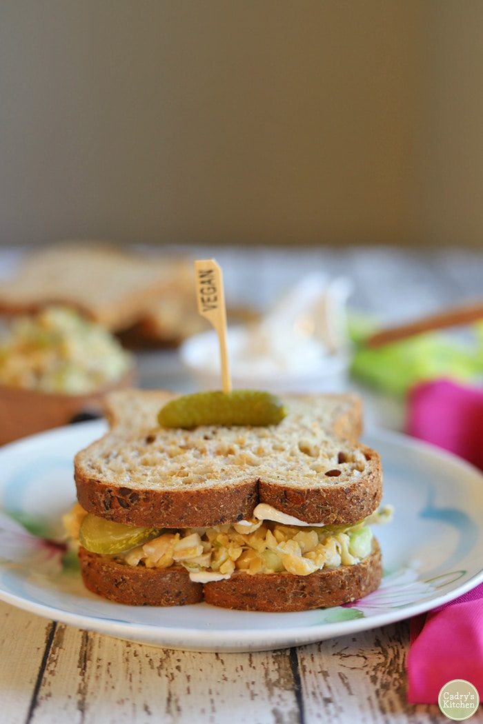 Chickpea tuna salad sandwich on plate with pickle speared on top.