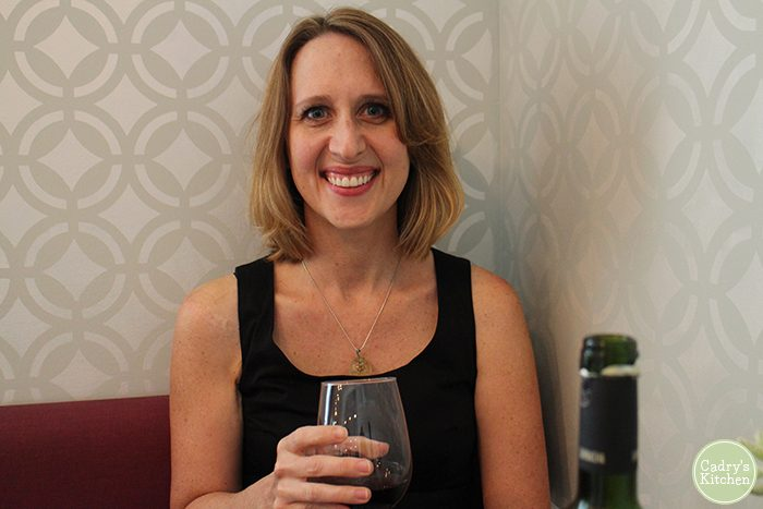 Cadry holding glass of wine in Modern Love.