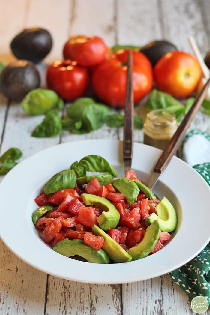 Bowl with avocado caprese salad. Avocados and tomatoes in background.