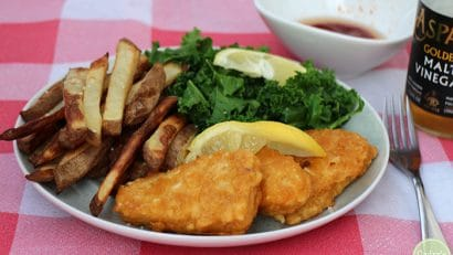 Gardein fishless filets on plate with lemon, fries, and kale.