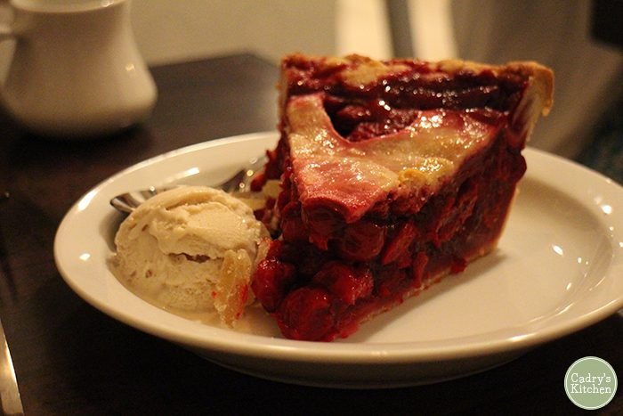 Slice of cherry pie on plate with ginger ice cream.