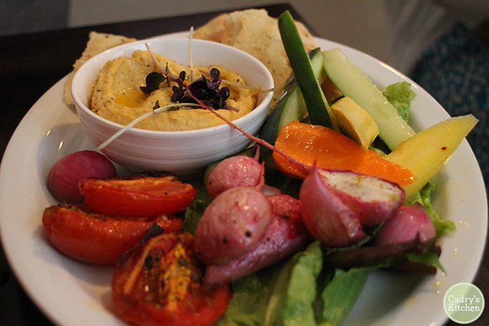 Hummus plate with radishes, peppers, cucumber, and tomatoes.