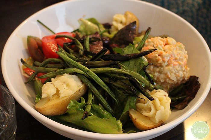 Nicoise salad with green beans and deviled potatoes in bowl.
