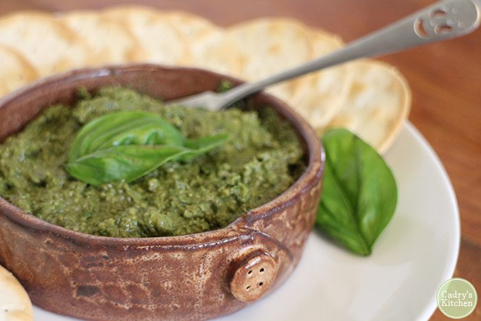 Basil dip with crackers on plate.