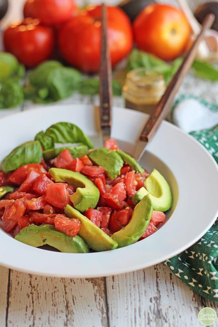 Vegan caprese salad in bowl with fresh basil.