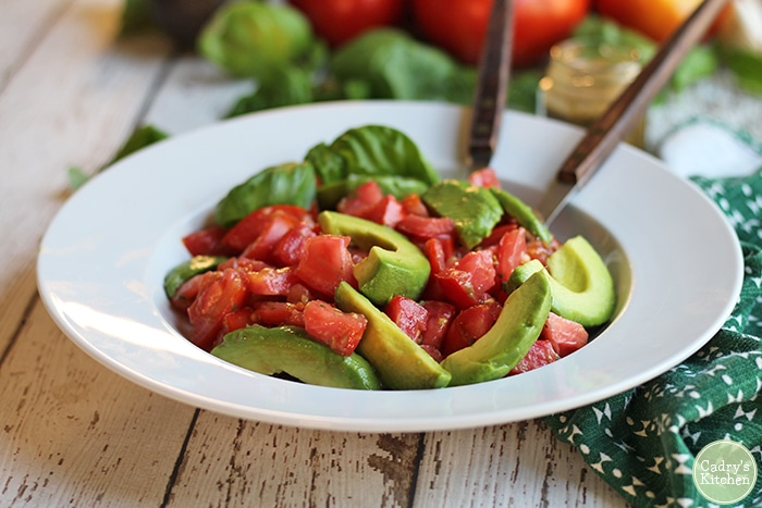 Avocado caprese salad in bowl. Avocado tomato salad with fresh basil.