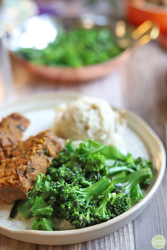 Broccolini and kale on plate with lentil loaf & mashed potatoes.