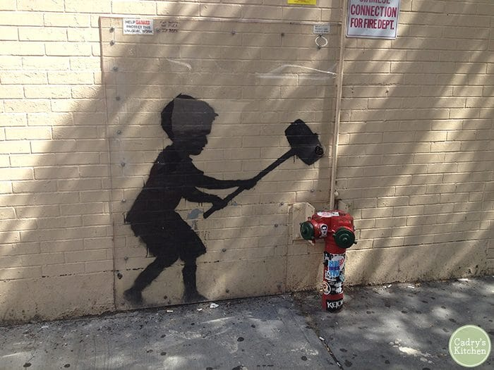 Banksy graffiti in NYC of a boy hitting a hydrant with a hammer.