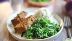Broccolini and kale on plate with mashed potatoes and lentil loaf.