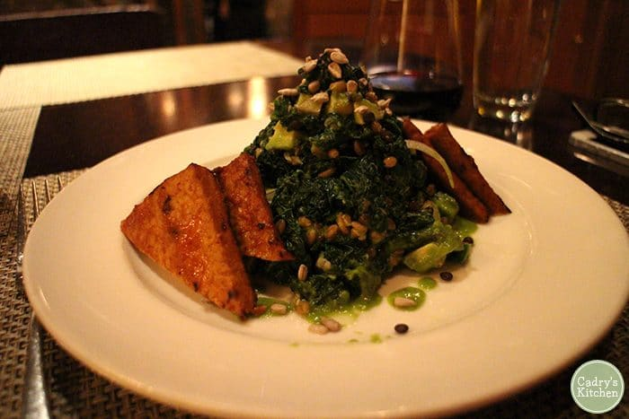 Grilled kale salad with grilled tempeh in bowl.