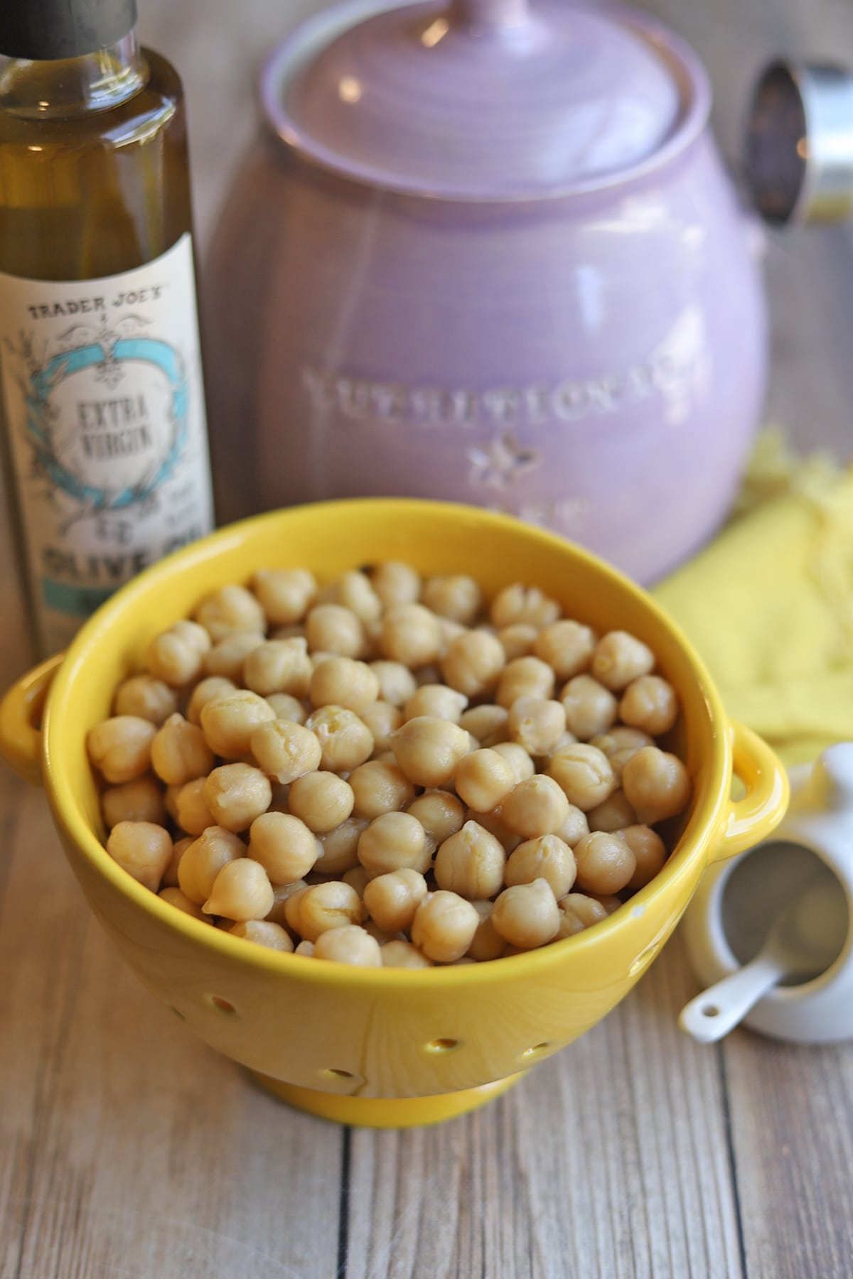 Garbanzo beans in colander by nutritional yeast flakes, oil, and salt.