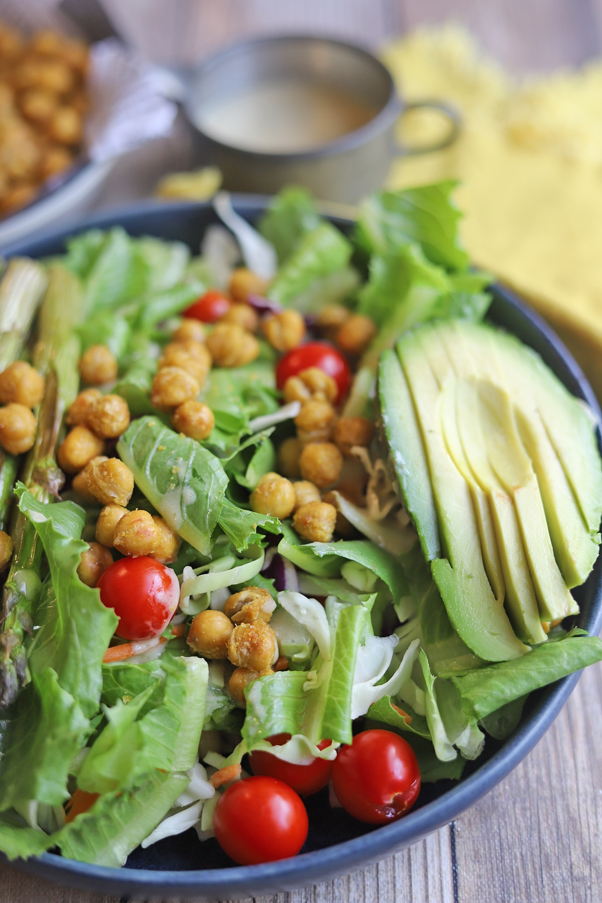 Salad with avocado and roasted chickpeas in blue bowl.