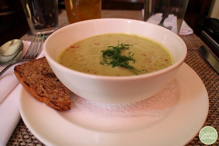Chilled avocado soup in bowl with bread.