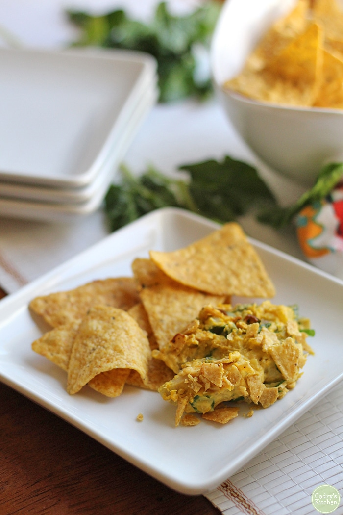 Vegan spinach artichoke dip on plate with tortilla chips.