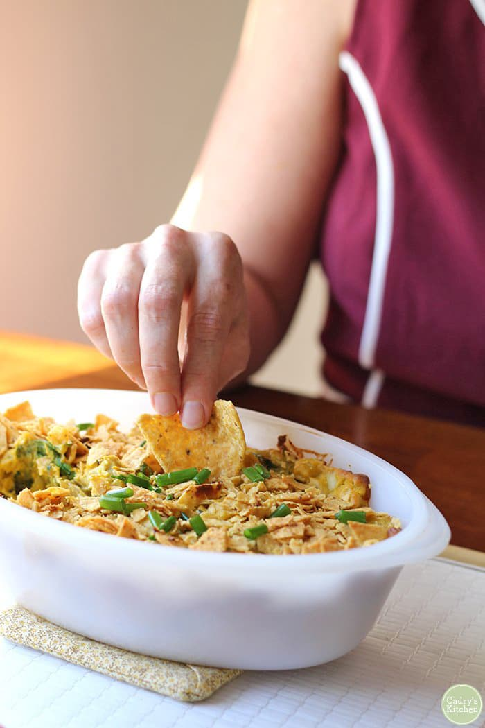 Hand dipping tortilla chip into dip covered with chips & green onions.