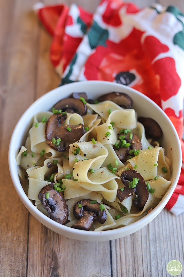 Buttery garlic noodles in bowl with mushrooms by flowered napkin.
