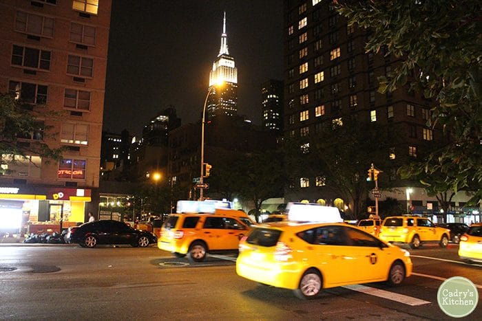 Taxi cabs on New York City street in front of the Empire State Building.