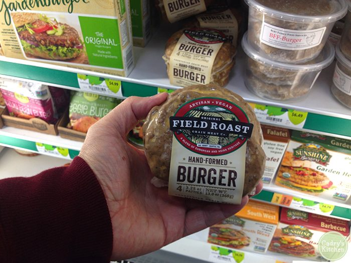 Hand holding package of Field Roast burgers at grocery store.
