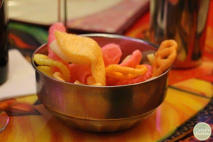 Crispy snacks in metal bowl.