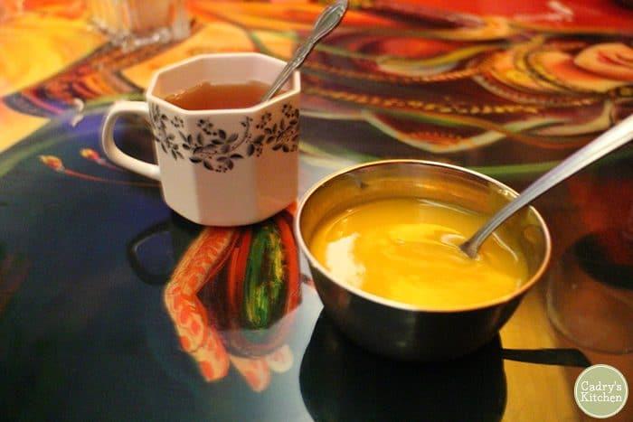 Mango puree vegan dessert with tea on table.