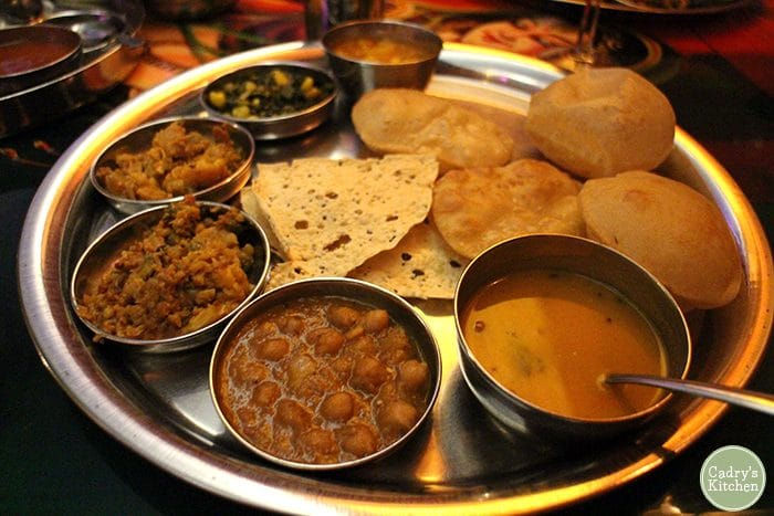 Curries and bread on metal tray.