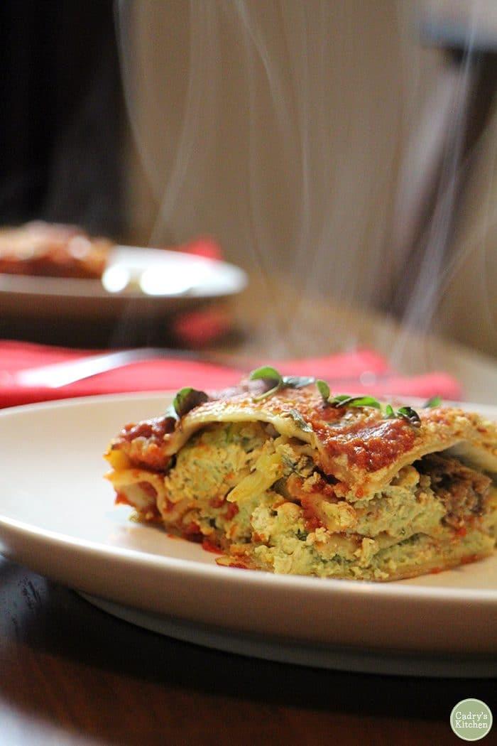 Slice of vegan lasagna steaming on a plate.