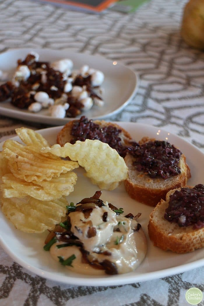 Vegan onion dip on plate with potato chips & olive tapenade.