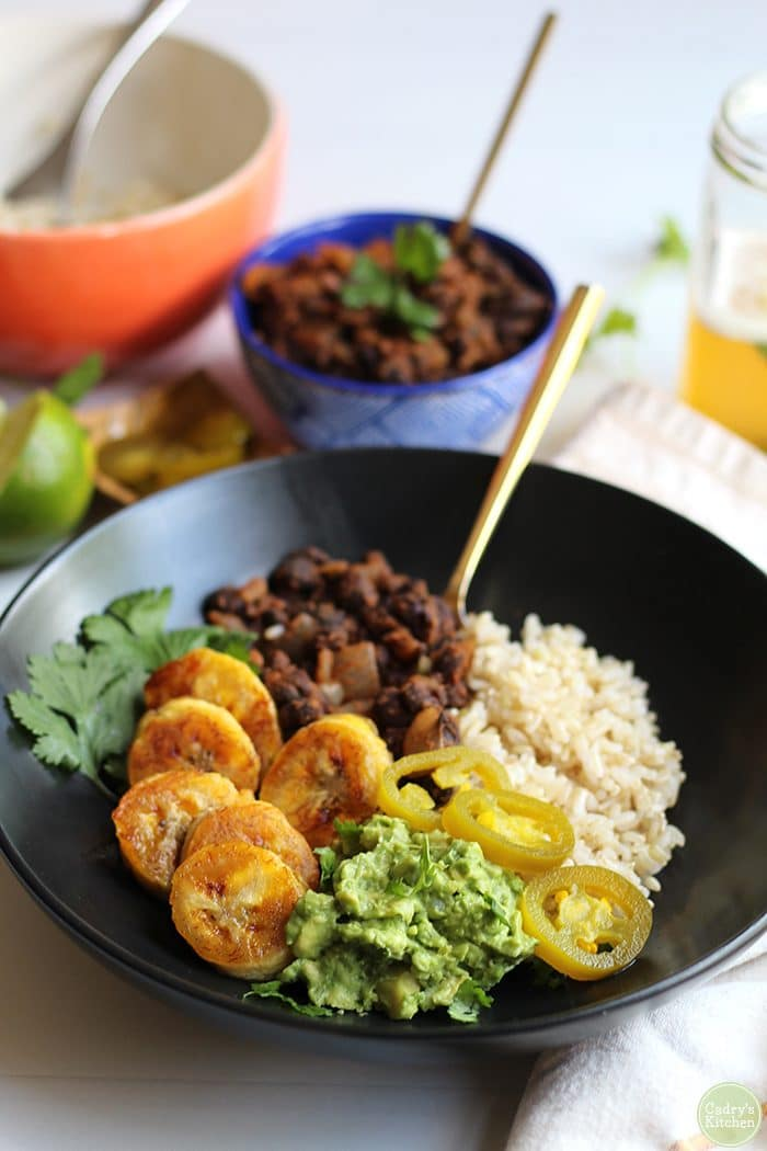 Vegan black bean bowl with brown rice, plantains, and guacamole.
