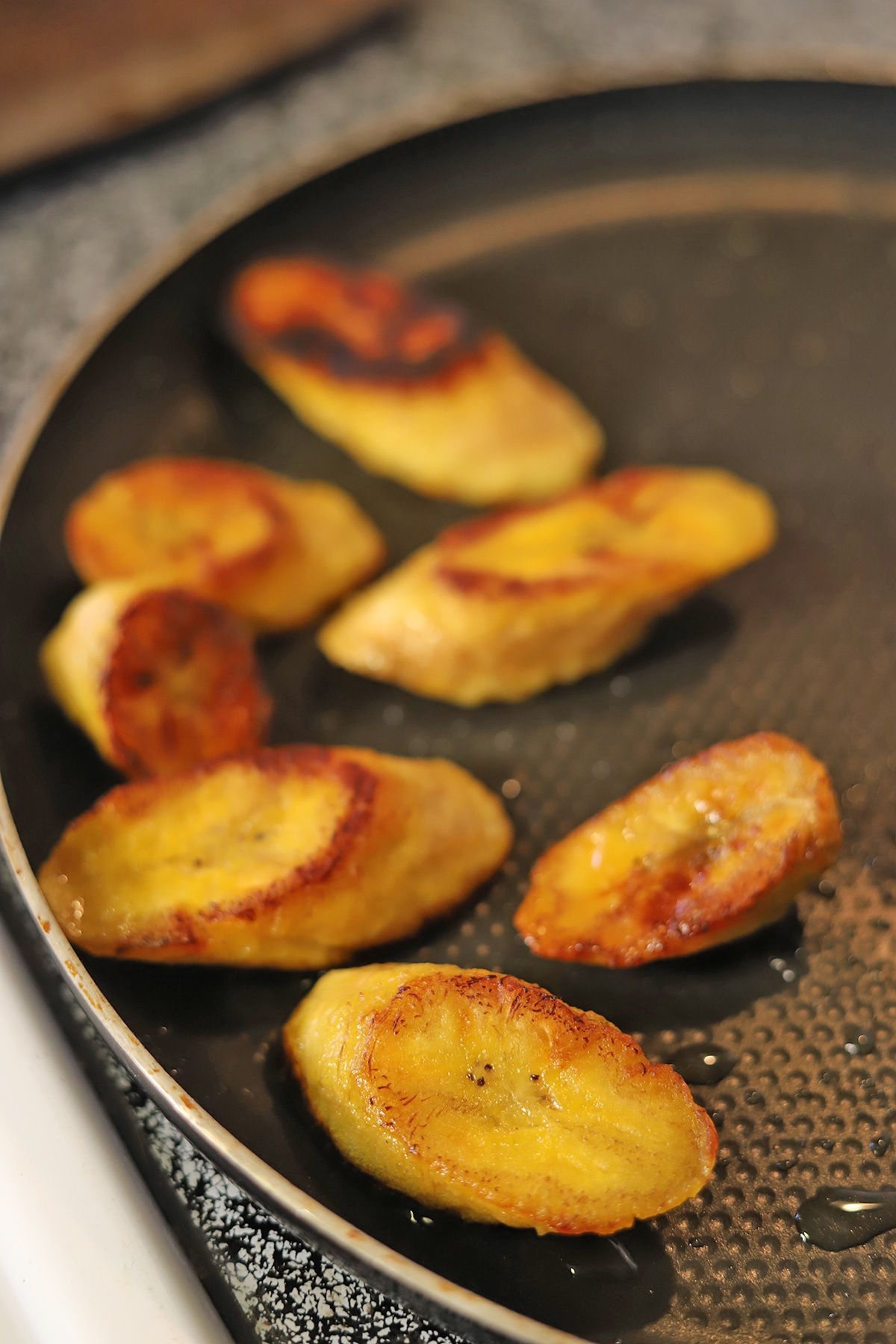 Plantains frying in skillet.