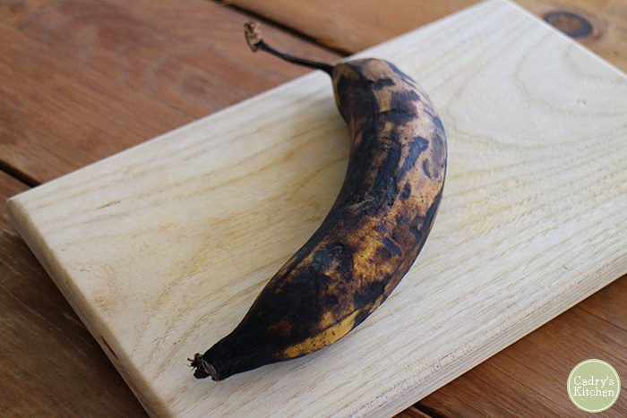 Plantain on cutting board with black peel.