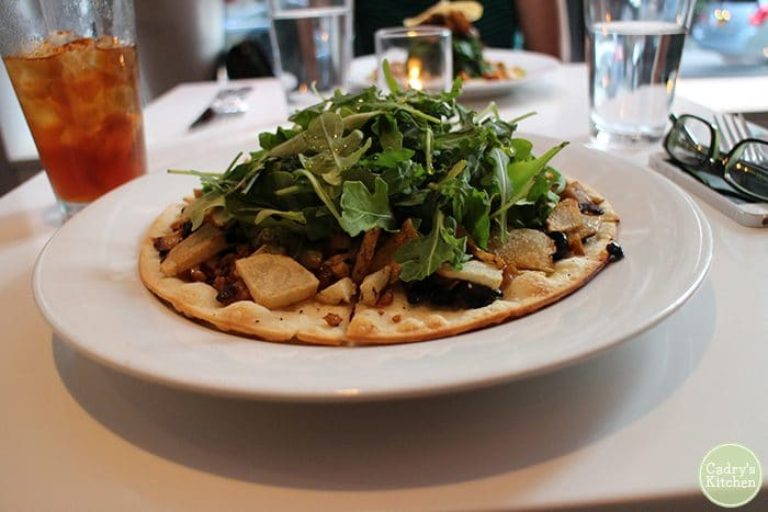 Roasted potatoes pizza with arugula on plate.