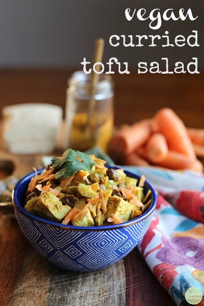 Bowl of vegan curried tofu salad with carrot, pistachios, and raisins + text.