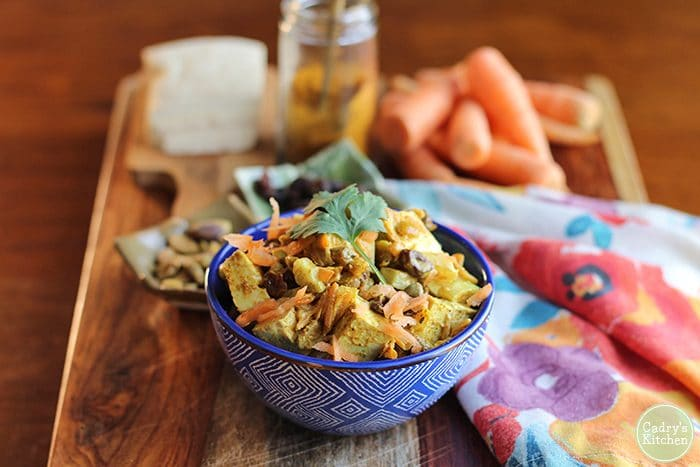 Blue bowl with curried tofu salad. Carrots, tofu, curry powder, and pistachios in background.